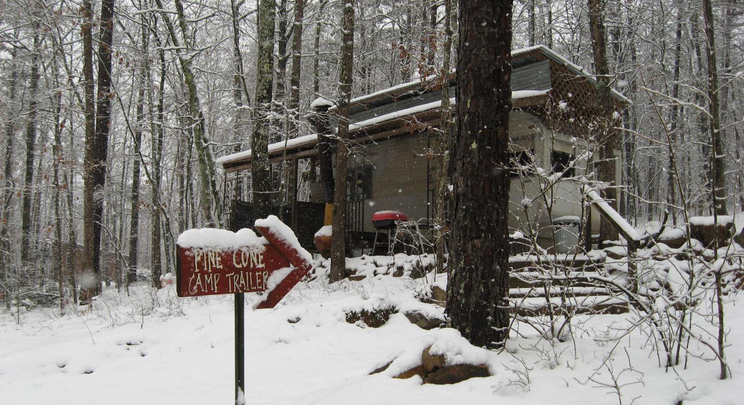 Exterior view of the cabin in the winter surrounded by white snow and the woods with bare trees
