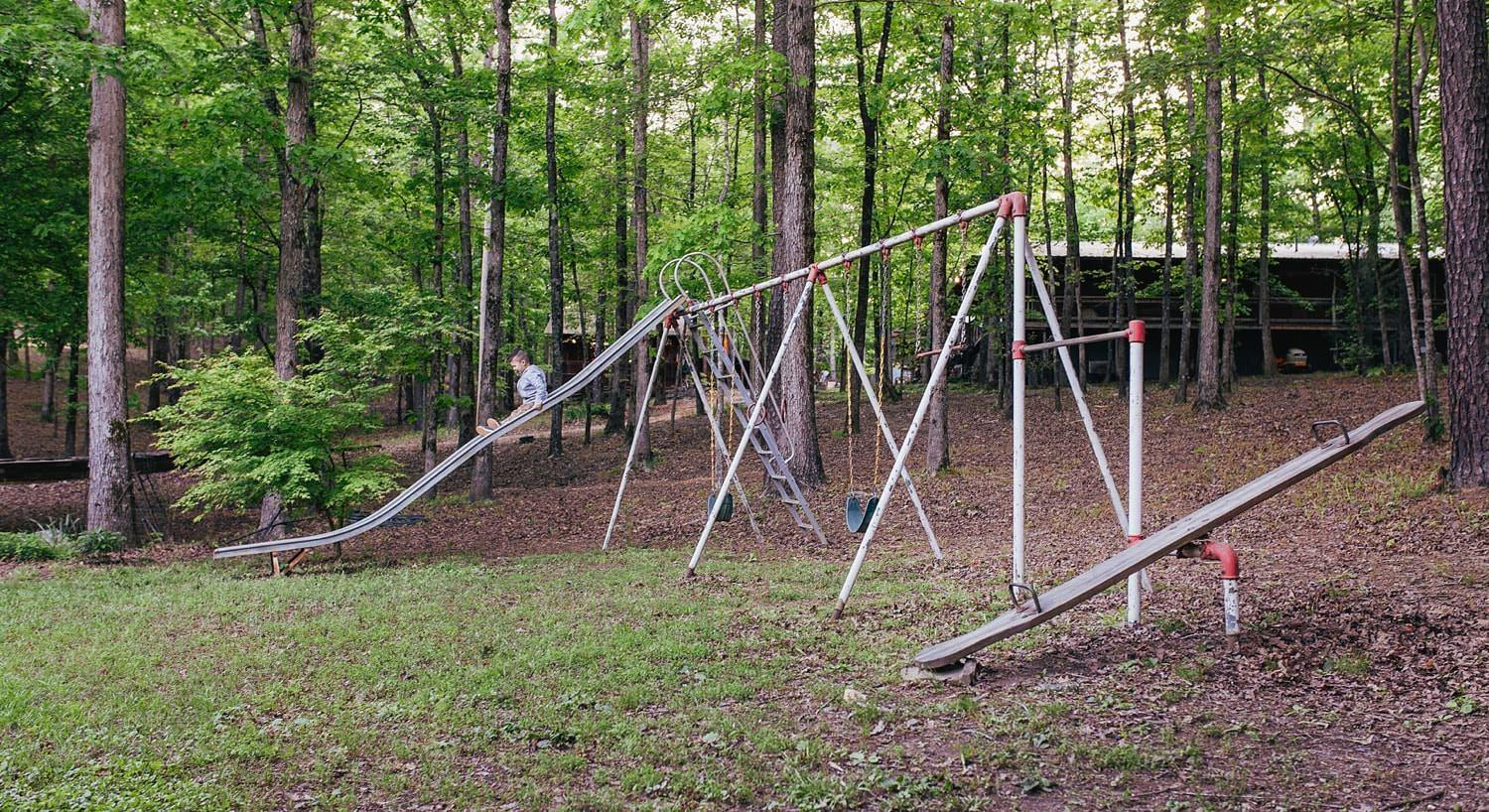 Little boy sliding down a slide on a playground set surrounded by trees