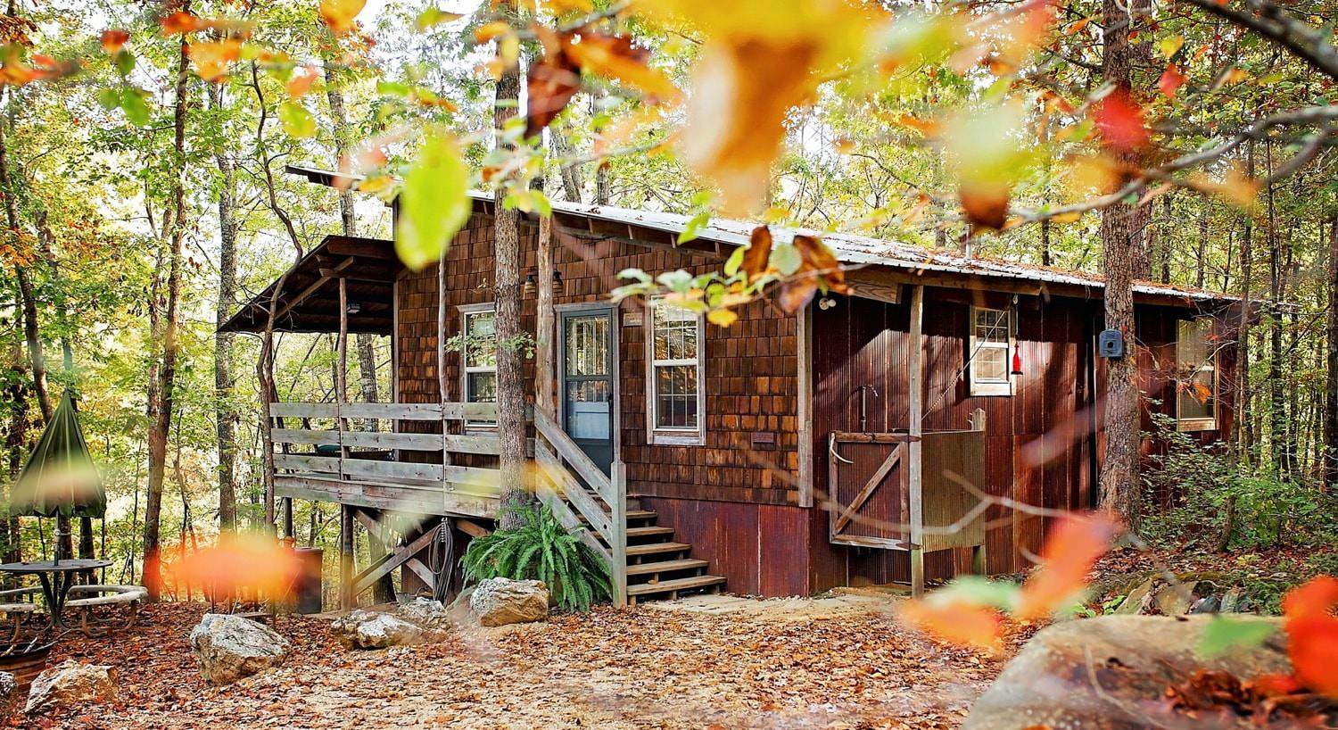 Exterior view of one of the cabins in the fall surrounded by trees with colorful autumn leaves