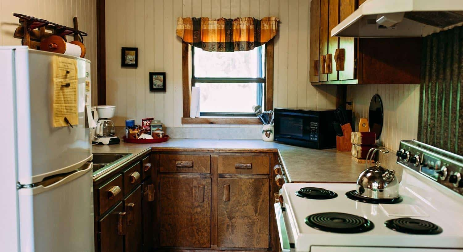 A kitchen in one of the cabins with refrigerator, range, countertop and window