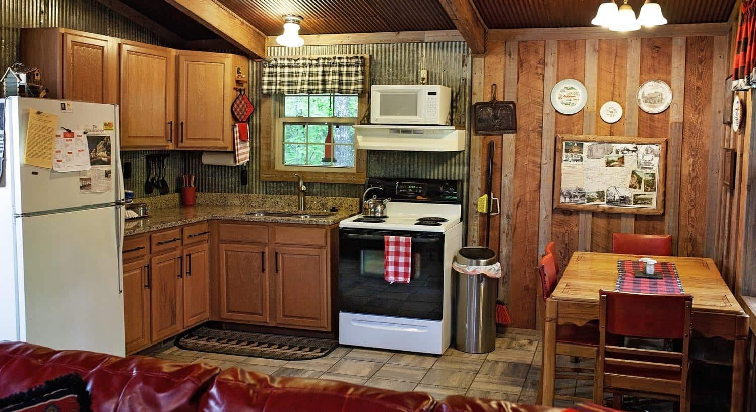 L-shaped kitchen in one of the cabins with window, refrigerator, range, countertop, and dining table for two