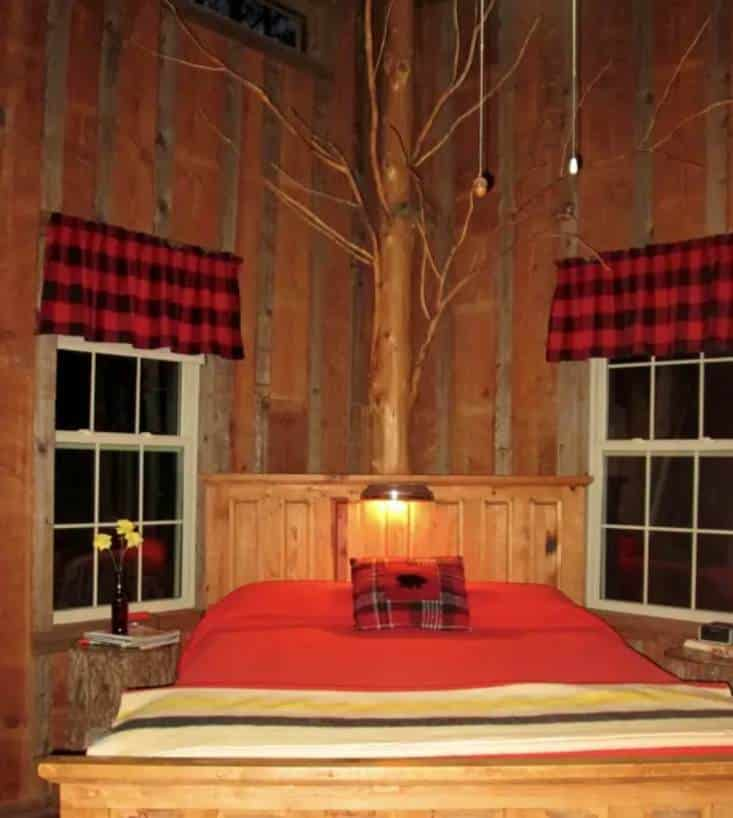Queen size bed in room with rustic wood walls and tall ceilings. Red bedspread.