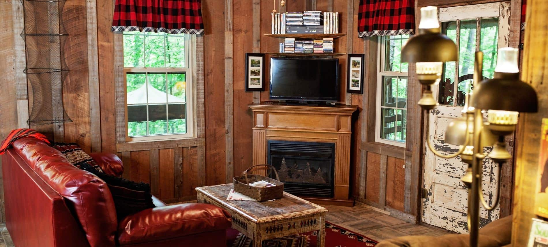 Wood cabin interior with corner fireplace, TV, several windows, and leather sofa with coffee table