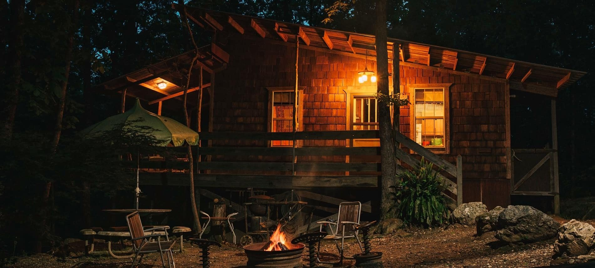Cabin exterior at night with round patio umbrella table and chairs around a warm glowing fire pit