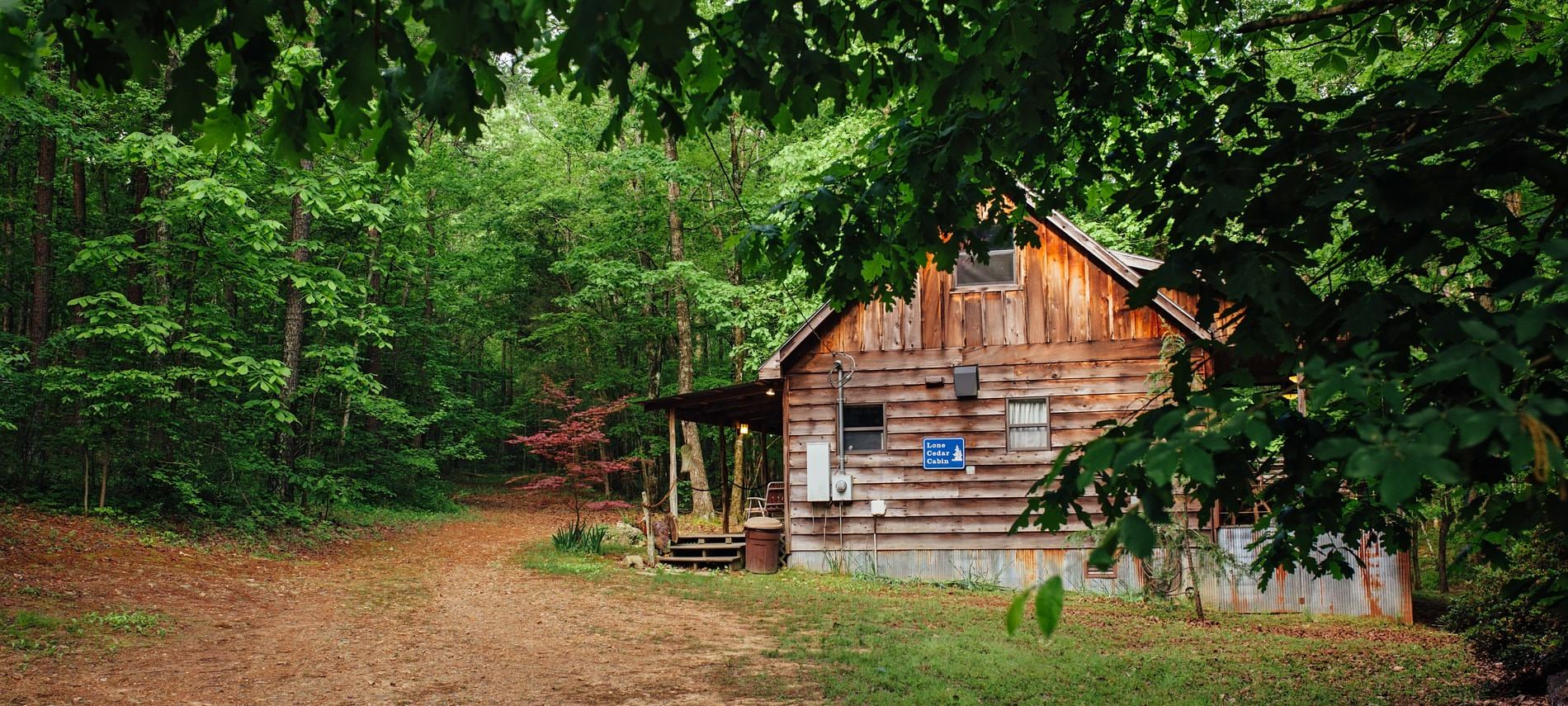 Exterior view of wooded cabin, side covered porch, surrounded by lush green trees