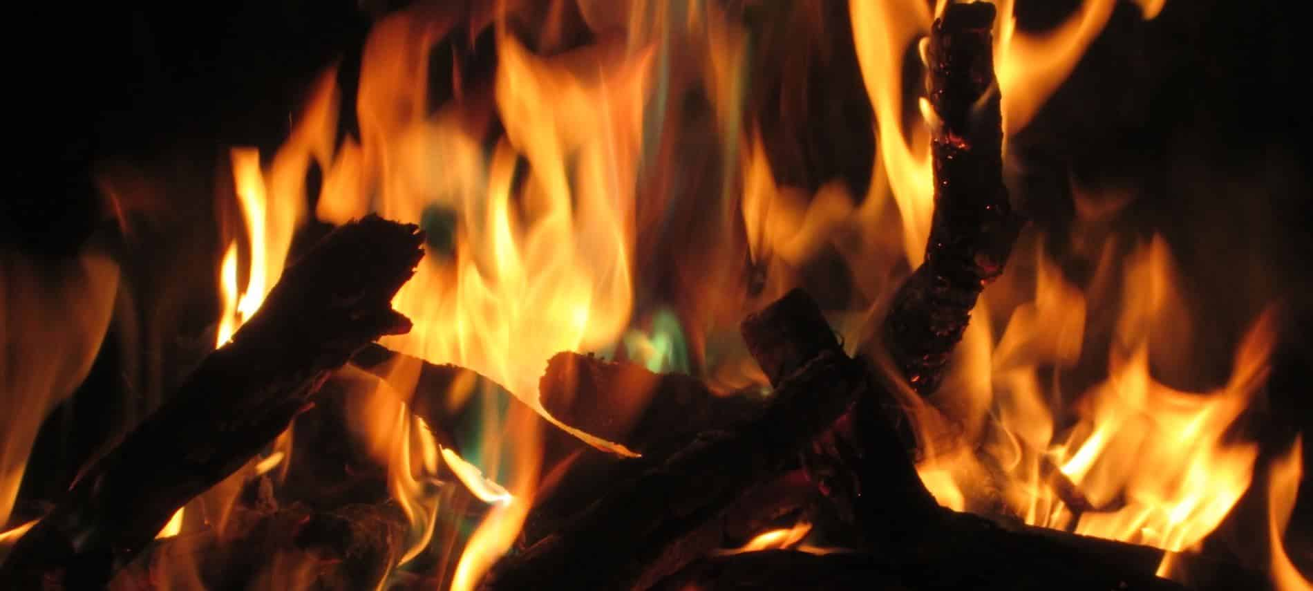 Close up view of an outdoor campfire with warm yellow and orange flames