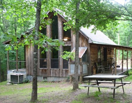 Exterior view of wooden cabin with gable roof, two side covered porches, a picnic table, surrounded by green leafy trees