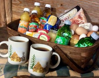 Brown basket filled with juice, tea, bacon, eggs, and more, with two cups of coffee set in front