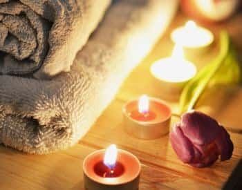 Close up view of folded towels, lit candles, and a red rose on a wooden table