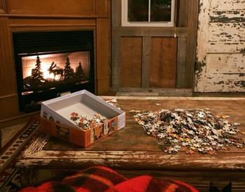 Interior of cabin with glowing corner fireplace and a puzzle on top of a rustic coffee table