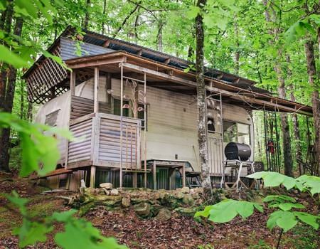Exterior of cabin and charcoal grill in the woods surrounded by trees with leafy green leaves
