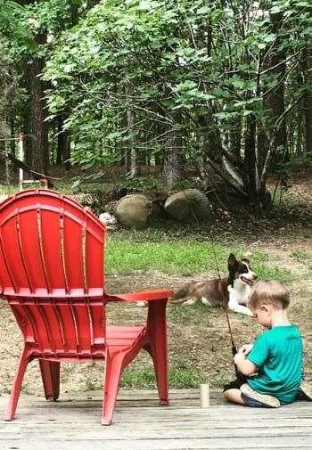 Little boy with fishing rod sitting on a wooden deck by a red chair and a brown and white dog