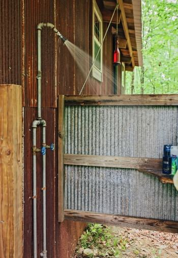 Outdoor shower under the eave surrounded by metal and wood walls