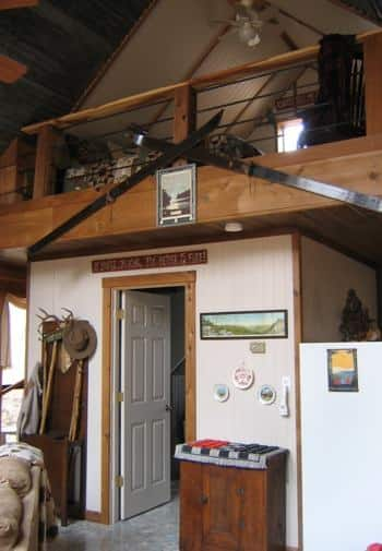Interior of cabin with fishing and outdoor decor, vaulted ceiling, and a loft with ceiling fan.