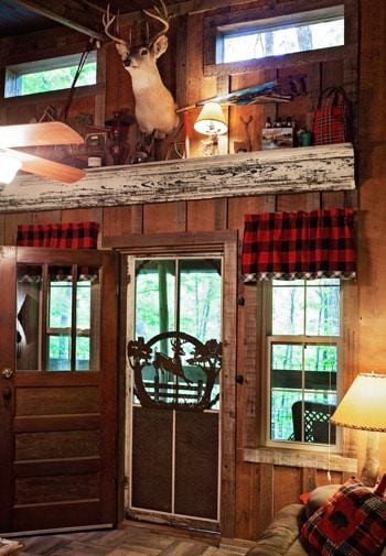Cabin interior with tall ceilings, windows, and deer head mounted on the wall