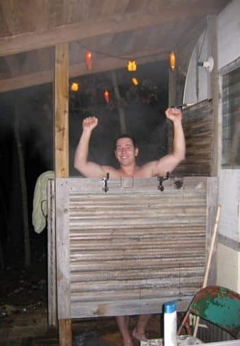 Smiling man standing inside an outdoor shower on the side of the cabin